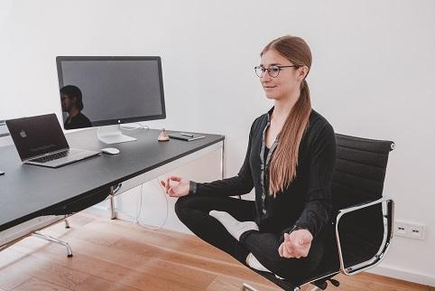 Business Yoga wird durch eine Frau im Schneidersitz auf einem Bürostuhl in Büroumgebung dargestellt.