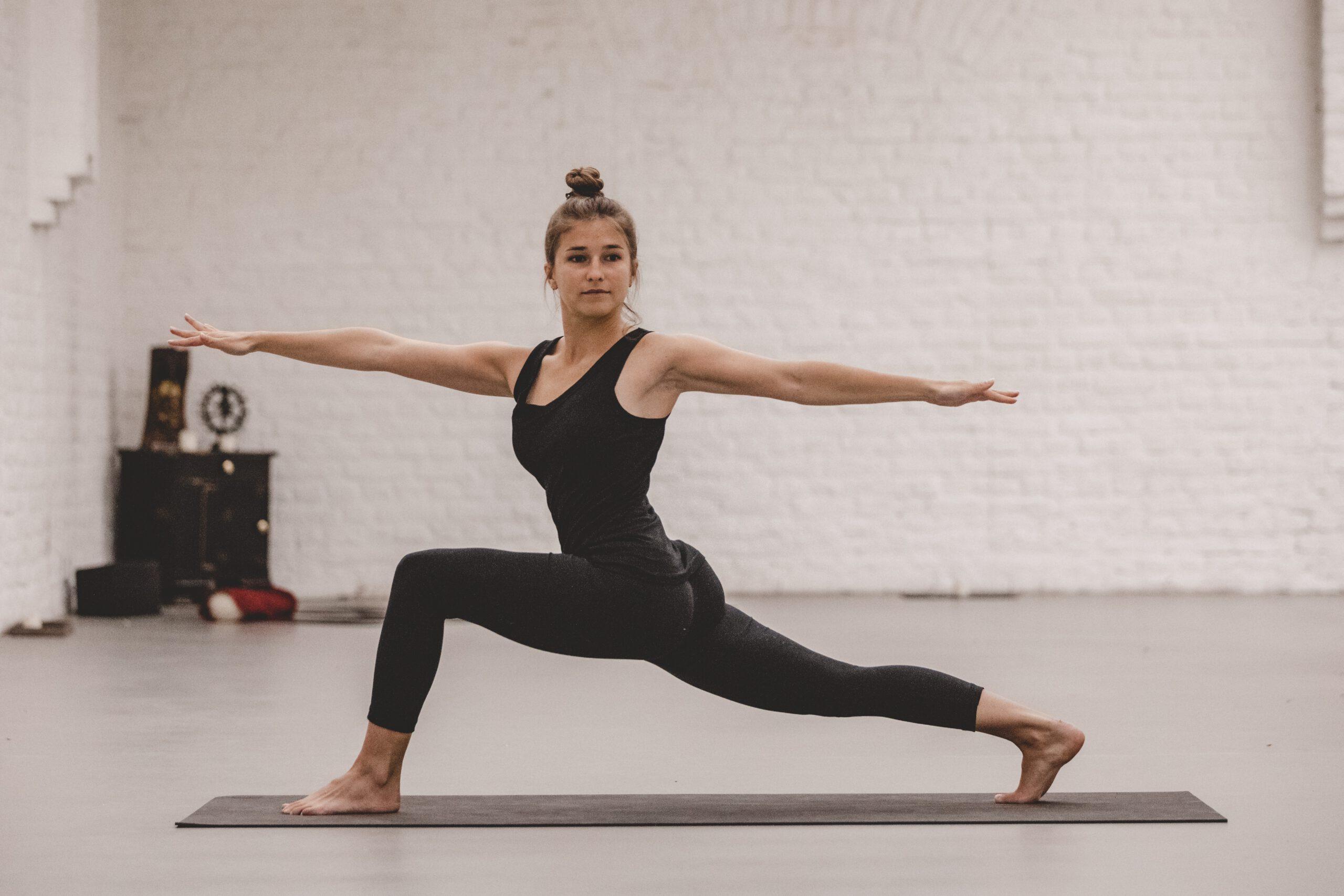 Yogalehrerin in einem Yogatsudio in der Position des gedrehten zweiten Kriegers (Ausfallschritt mit gehobenen und gedrehten Oberkörper).